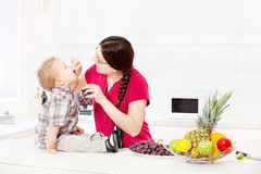 Mother feeding child in kitchen. Mother feeding child with grapes in kitchen Royalty Free Stock Images