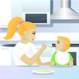Mother feeding child in kitchen Royalty Free Stock Photos