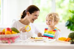 Mother feeding child. Mom feeds kid vegetables stock photography