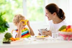 Mother feeding child. Mom feeds kid vegetables stock photos