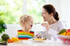 Mother feeding child. Mom feeds kid vegetables stock images