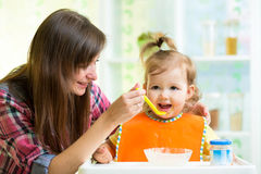 Mother feeding child with spoon indoors Royalty Free Stock Images