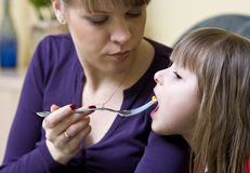Mother feeding daughter stock photography