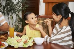 Mother feeding daughter stock images