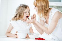 Mother feeding daughter with muesli and raspberries Royalty Free Stock Image