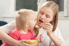 Mother feeding daughter with porridge Stock Photos