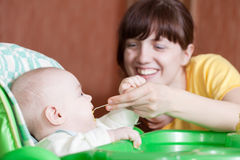 Mother feeding daughter with spoon. Mother feeding her 6 month old daughter with spoon royalty free stock photo