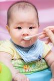 Mother feeding her asian thai baby girl Stock Photo