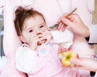 Mother feeding her baby apple puree Stock Images