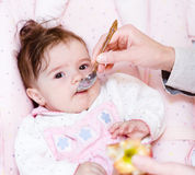 Mother feeding her baby apple puree Royalty Free Stock Images