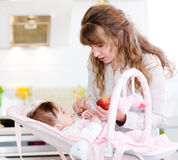 Mother feeding her baby apple puree Royalty Free Stock Photos