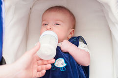 Mother feeding her baby from a bottle Stock Photography