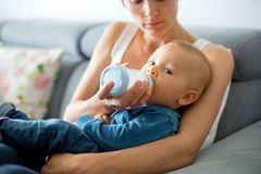 Mother, feeding her baby boy from bottle, sitting on the couch a Royalty Free Stock Photos