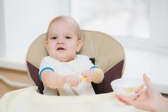 Mother feeding her baby breast porridge day Royalty Free Stock Photos