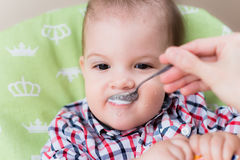 Mother feeding her baby breast porridge day Royalty Free Stock Images