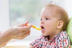 Mother feeding her baby breast porridge day Stock Photo