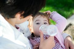 Mother feeding her baby girl with feeding bottle Stock Image