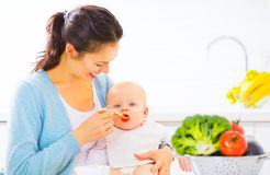 Mother feeding her baby girl with a spoon Stock Photo