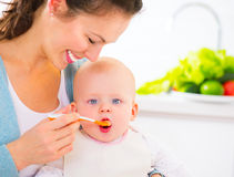 Mother feeding her baby girl with a spoon Stock Images