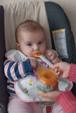 Mother is feeding her baby in the highchair at home. Stock Photo