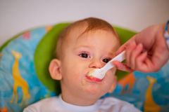 Mother is feeding her baby in the highchair at home royalty free stock image
