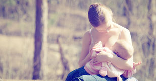 Mother Feeding Her Baby In Nature Outdoors In The Park Stock Image