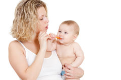 Mother feeding  her baby by spoon. Over white background Royalty Free Stock Photo