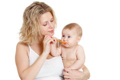 Mother feeding  her baby by spoon. Over white background Stock Photo