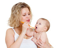 Mother feeding  her baby by spoon isolated Royalty Free Stock Images