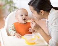 Mother feeding her baby with spoon. Mother giving healthy food to her adorable child at home stock photos