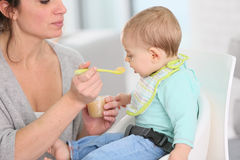 Mother feeding her child with stewed fruits Stock Photo