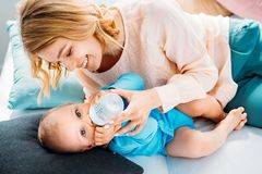Mother feeding her little child with baby bottle while lying on bed. At home royalty free stock images