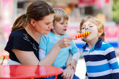 Mother feeding her little kid boys with ice cream Stock Photography