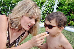 Mother feeding her little son with grape Royalty Free Stock Photos