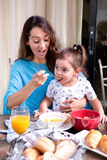 Mother feeding her little toddler girl sitting on her lap. Beautiful young mother feeding her little toddler girl sitting on her lap, breakfast cereal at outdoor Stock Images
