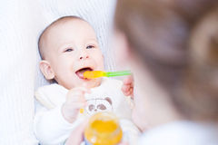Mother feeding her lovely baby boy with spoon Stock Photo