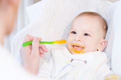 Mother feeding her lovely baby boy with spoon Royalty Free Stock Photos