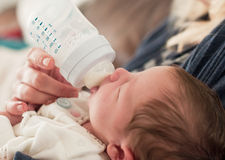 Mother feeding her new born baby. Mother feeding a bottle of milk to her new born baby Royalty Free Stock Photo