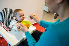 Baby eating solid food from a spoon. diversification. Mother feeding her six month old baby son, giving him his first solid food, healthy vegetable pure from stock photo