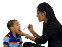 Mother feeding her son Stock Photos
