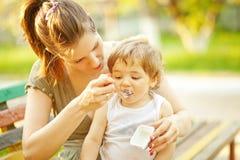 Mother feeding her son Royalty Free Stock Photos