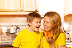 Mother feeding her son with piece of pizza. Cheerful mother feeding her smiling son with one hand with piece of pizza in the kitchen stock photo