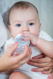 Mother feeding his baby boy by milk from bottle Stock Image