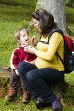 Mother feeding his boy outside in forest Stock Photography