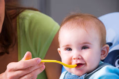 Mother feeding hungry baby stock image