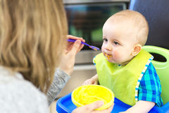Mother feeding hungry baby in the highchair indoors Stock Images