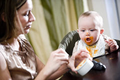 Mother feeding hungry baby solid food. Mother feeding hungry six month old baby solid food Royalty Free Stock Image