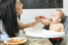 Mother feeding hungry six month old baby solid Royalty Free Stock Photo