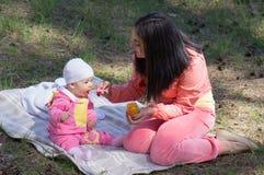 Mother feeding infant baby Stock Image