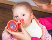 Mother feeding infant girl Stock Images